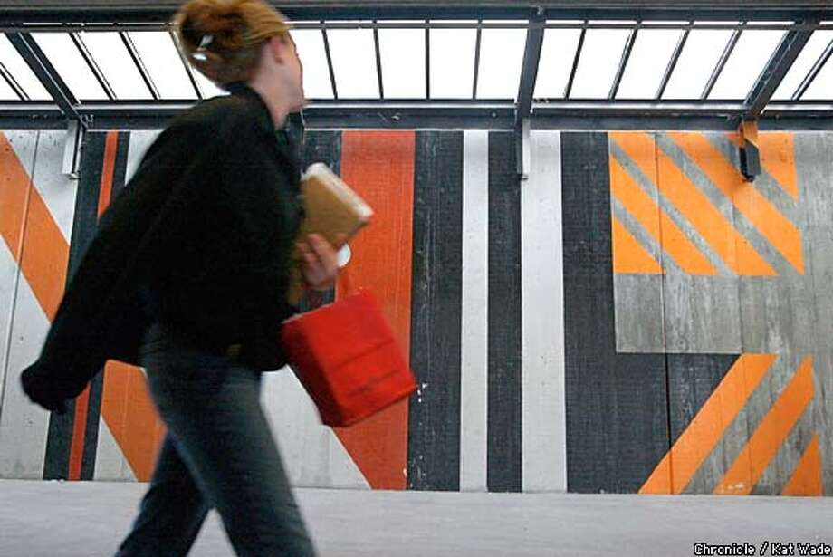 A BART passenger passes by the 100-foot-by-16-foot mural by San Francisco artist Win Ng that decorates the wood-and-concrete structure at the Orinda station. Chronicle photo by Kat Wade