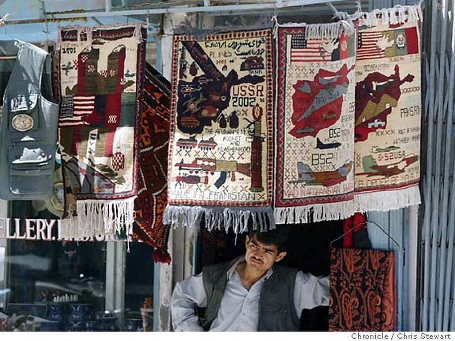 Event on 4/17/04 in Kabul.  A merchant sells Afghan war rugs in his Kabul, Afghanistan shop on Chicken Street, a popular tourist street of handicrafts shops. A few years ago, just after 9/11, curious images began cropping up on the traditinal rugs woven in Afghanistan. Instead of the usual birds, trees and pots, many rugs began depicting tanks, fighter jets and missles -- long familiar sights in the war-torn country. Others show the smoking Twin Towers -- tiny bodies falling out of them. Despite their controversial images, the rugs are growing in popularity and in some circles have garnered a cult following. Chris Stewart / The Chronicle Photo: Chris Stewart