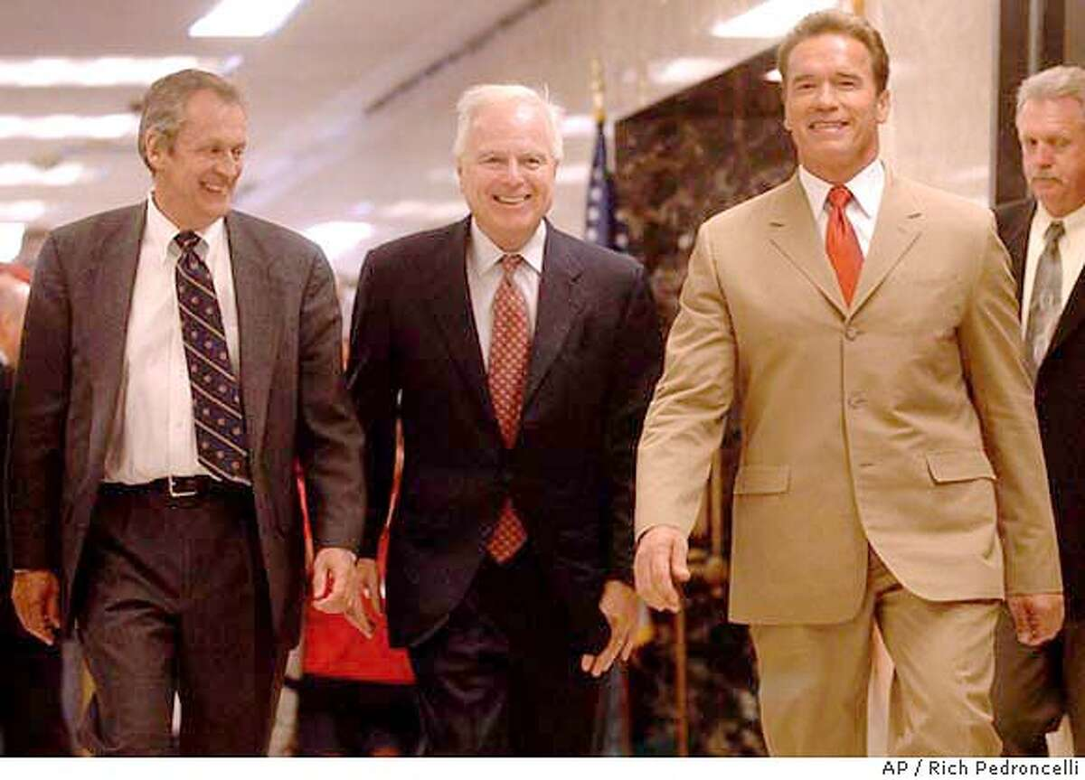 Gov. Arnold Schwarzenegger, right, accompanied by University of California President Robert Dynes, left, and Education Secretary Richard Riordan, center, walk to a Capitol news conference where he announced an agreement with state university officials on funding cuts and enrollment caps, held in Sacramento, Calif., Tuesday, May 11, 2004. Schwarzenegger's plan, which needs approval by the Legislature, would cut in half a proposed 40 percent hike in fees imposed on graduate students while raising otherstudent fees by 10 percent over three years.(AP Photo/Rich Pedroncelli)