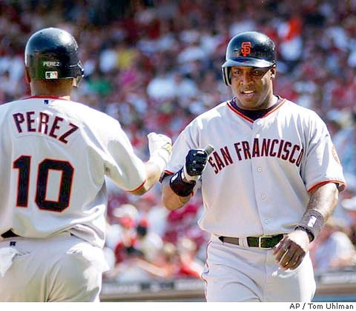 San Francisco Giants' Barry Bonds, right, is congratulated at home plate by Neifi Perez, left, after scoring the go-ahead run on a Deivi Cruz sacrifice fly off Cincinnati Reds' Danny Graves in the 10th inning, Sunday, May 9, 2004, in Cincinnati. The Giants won 7-6. (AP Photo/Tom Uhlman)