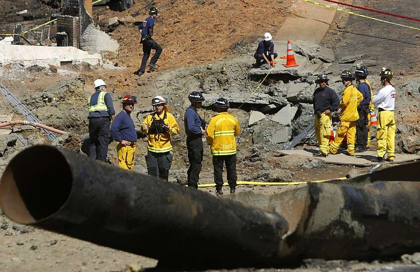 Firefighters and investigators stand at the edge of a large crater in San Bruno on Saturday. A 40-foot section of the natural gas pipeline that exploded Thursday came to rest several yards away on Glenview Drive.