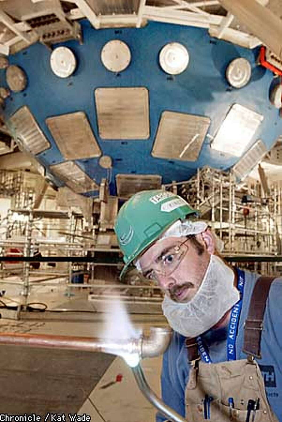 Neal Fouts with Kenetics mechanical contractor welds some pipe with the huge target chamber of the new NIF (National Ignition Facility) at the Lawrence Livermore Lab in the background. SAN FRANCISCO CHRONICLE PHOTO BY KAT WADE
