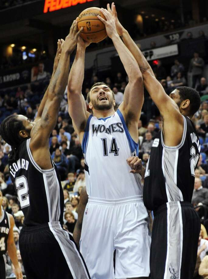 Minnesota Timberwolves' Nikola Pekovic (14), of Montenegro, shoots between San Antonio Spurs' Tim Duncan, right, and Kawhi Leonard in the first half of an NBA basketball game, Friday, Jan. 27, 2012, in Minneapolis. (AP Photo/Jim Mone)