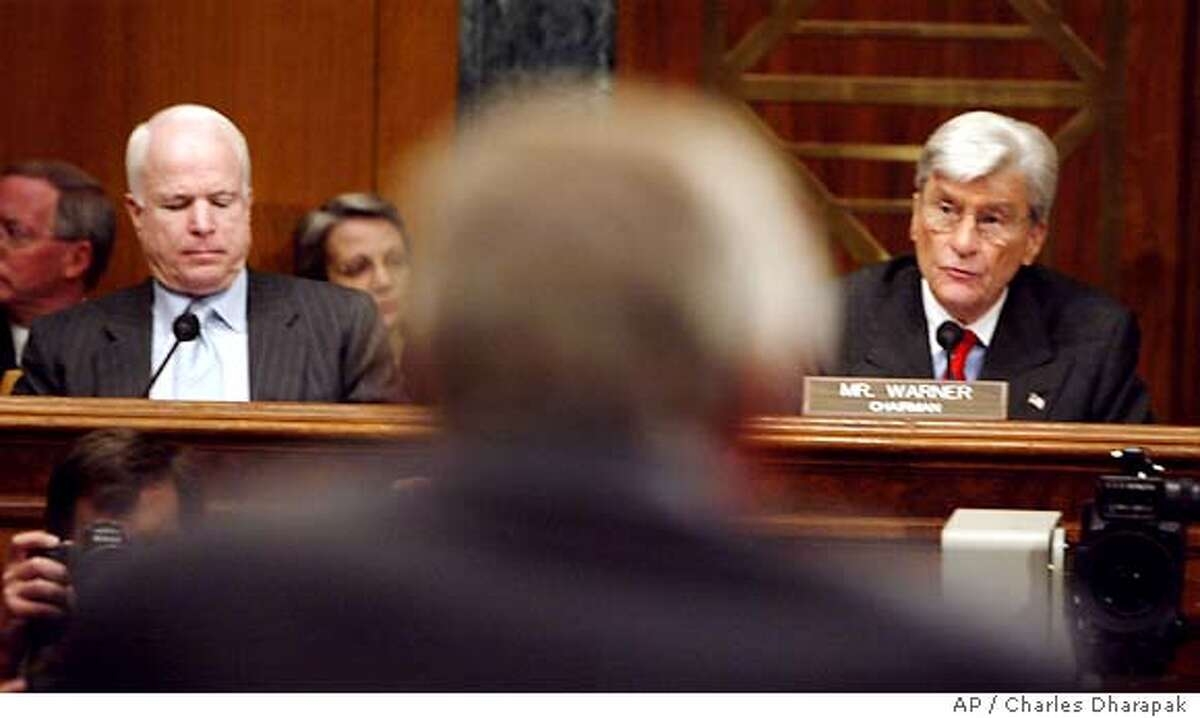 Defense Secretary Donald H. Rumsfeld, back to camera, is seen on Capitol Hill Friday, May 7, 2004, between Senate Armed Services Committee Chairman Sen. John Warner, R-Va., right, and committee member Sen. John McCain, R-Ariz. prior to testifying before the committee's hearing on prisoner abuse in Iraq. (AP Photo/Charles Dharapak)