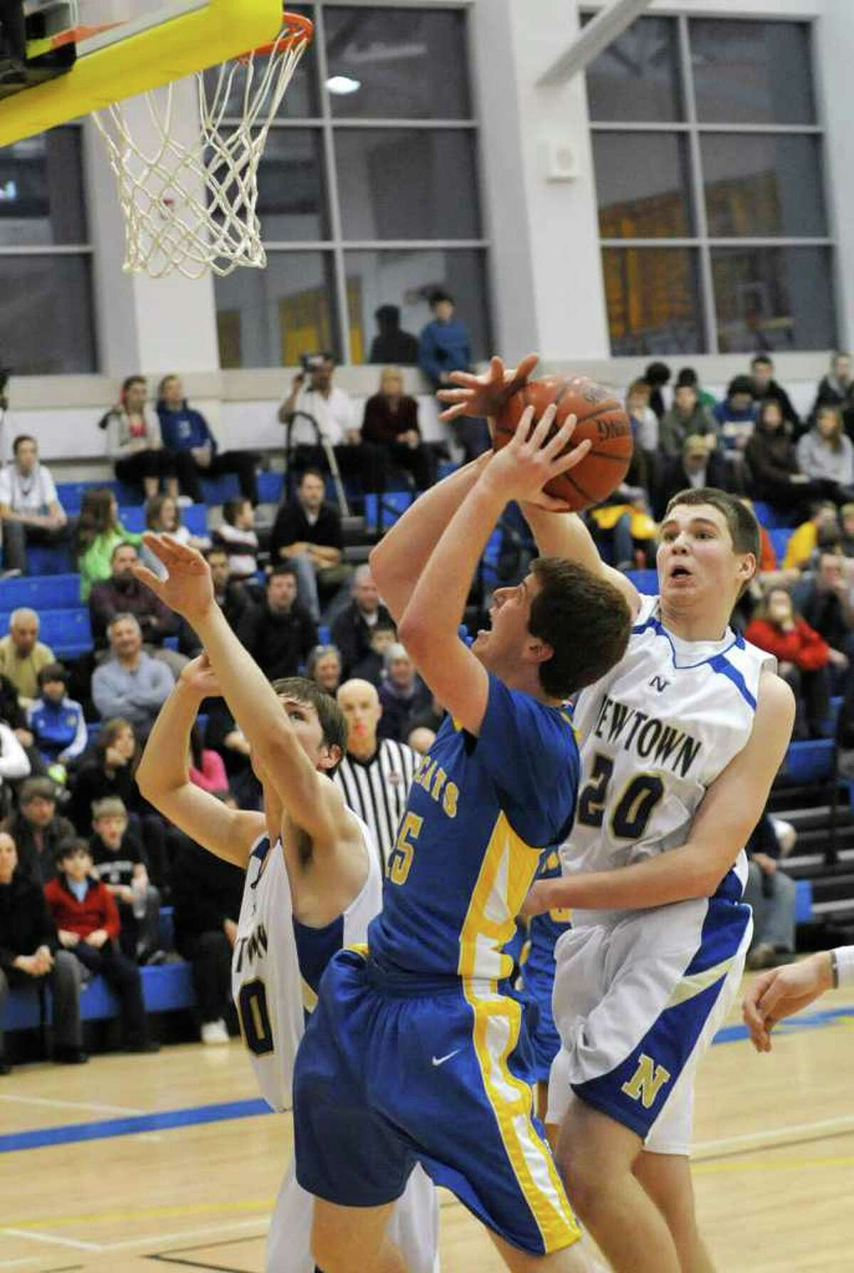 Newtown's Mike Davis blocks the shot of Brookfield's Danny Burkhart during their game at Newtown High School on Friday, Jan. 27, 2012. Newtown won 66-50.