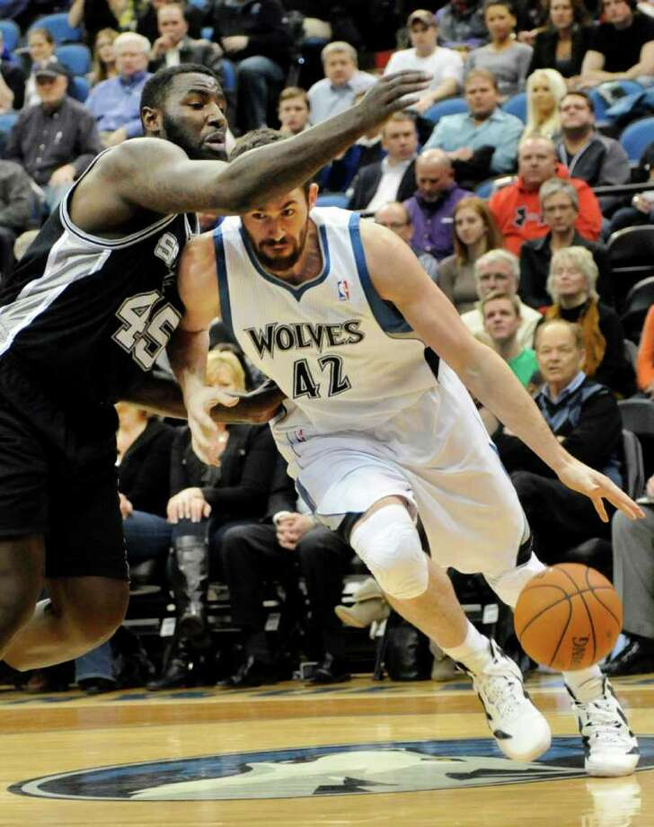Minnesota Timberwolves' Kevin Love (42) drives around San Antonio Spurs' DeJuan Blair in the first half of an NBA basketball game, Friday, Jan. 27, 2012, in Minneapolis. (AP Photo/Jim Mone) Photo: Associated Press
