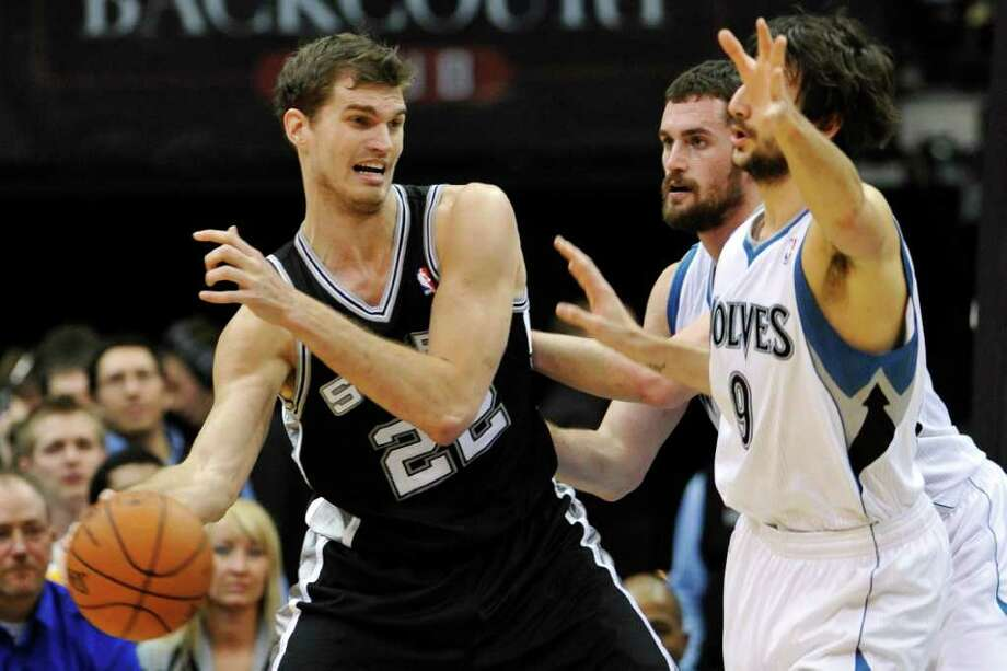 San Antonio Spurs' Tiago Splitter, of Brazil, left, passes around Minnesota Timberwolves' Ricky Rubio, of Spain, right, and Kevin Love during the first half of an NBA basketball game, Friday, Jan. 27, 2012, in Minneapolis. (AP Photo/Jim Mone) Photo: Associated Press