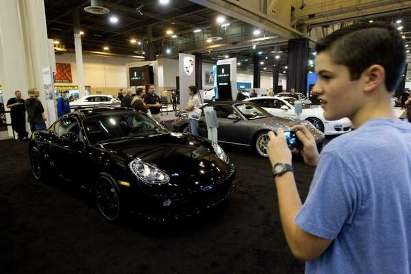 Jacob Poteet gets up close to appreciate a gleaming black Porsche at the auto show's Ultra Luxury Boutique.