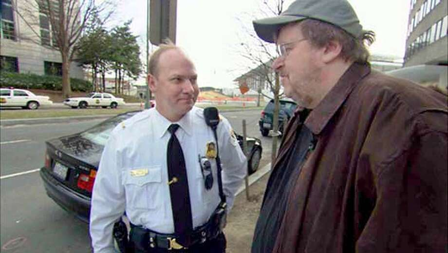 Michael Moore, right, and a Saudi Embassy guard in Washington talk in a scene from the movie. Associated Press Photo