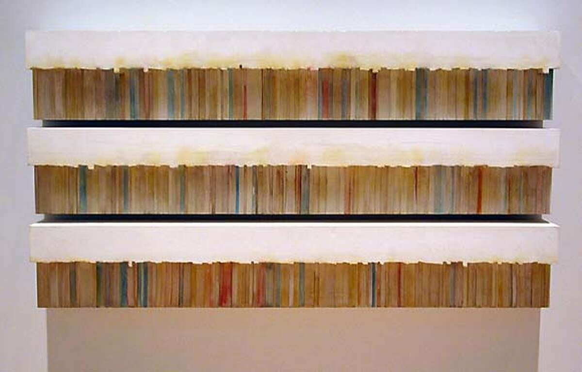 """Rachel Whiteread's """"Untitled (Fiction)"""" (1997) solidifies the spaces above and behind three shelves of paperbacks."""