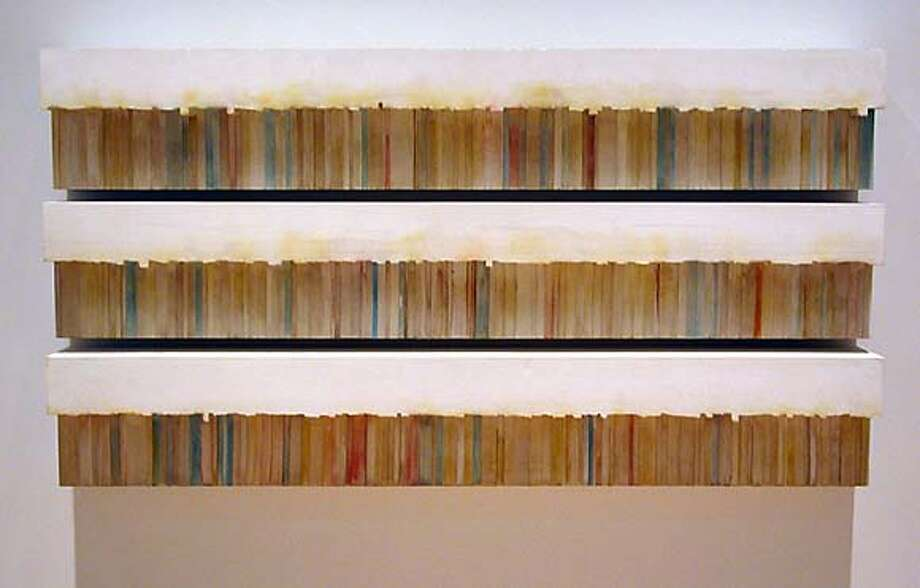 "Rachel Whiteread's ""Untitled (Fiction)"" (1997) solidifies the spaces above and behind three shelves of paperbacks."