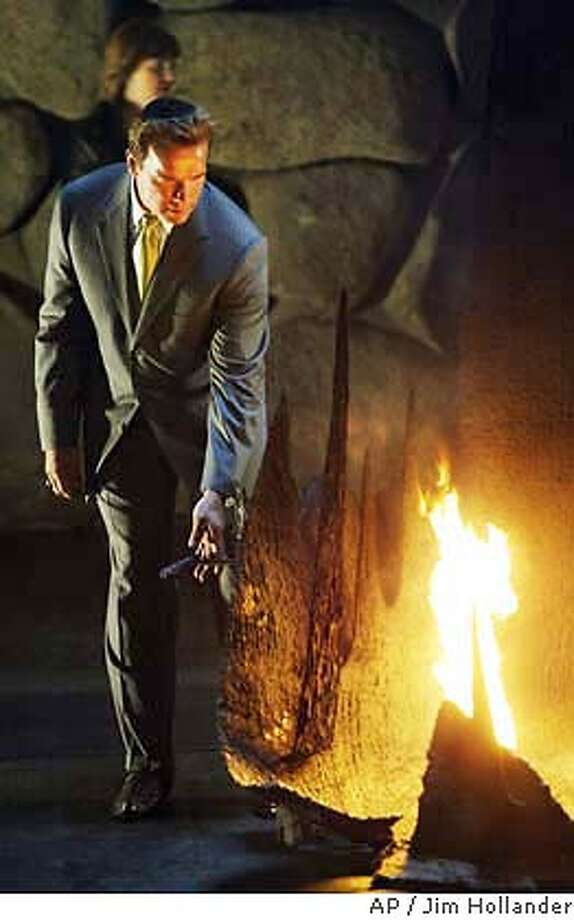 California Governor Arnold Schwarzenegger stands next to the Eternal Flame in the Hall of Remembrance in the Yad Vashem Holocaust Memorial in Jerusalem on Sunday, May 2, 2004 as he pays his respects to the six-million Jews exterminated by the Nazis during World War II. Earlier Schwarzenegger had met Israeli officials, including the prime minister and took part in a ground-breaking ceremony for a center of tolerance. (AP Photo/Jim Hollander, Pool) Photo: JIM HOLLANDER