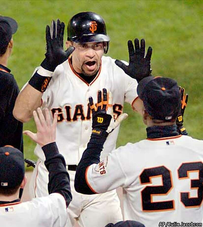 San Francisco Giants' Benito Santiago celebrates with teammates, including Shawon Dunston (23), after hitting what proved to be the game-winning home run against the St. Louis Cardinals in the eighth inning of game 4 of the NLCS in San Francisco, Sunday, Oct. 13, 2002. (AP Photo/Julie Jacobson) Photo: JULIE JACOBSON