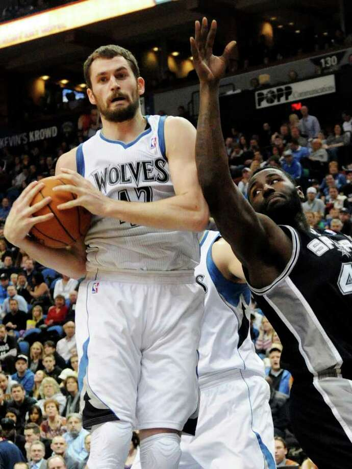 Minnesota Timberwolves' Kevin Love, left, grabs a rebound in front of San Antonio Spurs' DeJuan Blair during the second half of an NBA basketball game, Friday, Jan. 27, 2012, in Minneapolis. The Timberwolves won 87-79. (AP Photo/Jim Mone) Photo: Associated Press