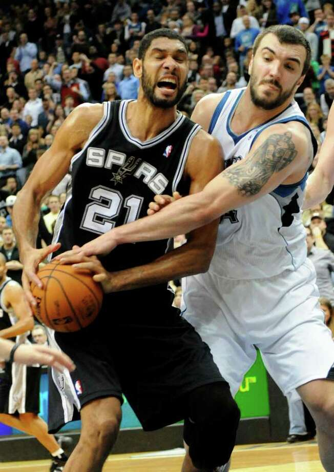 San Antonio Spurs' Tim Duncan (21) protects the ball from Minnesota Timberwolves' Nikola Pekovic, of Montenegro, in the second half of an NBA basketball game, Friday, Jan. 27, 2012, in Minneapolis. The Timberwolves won 87-79. (AP Photo/Jim Mone) Photo: Associated Press