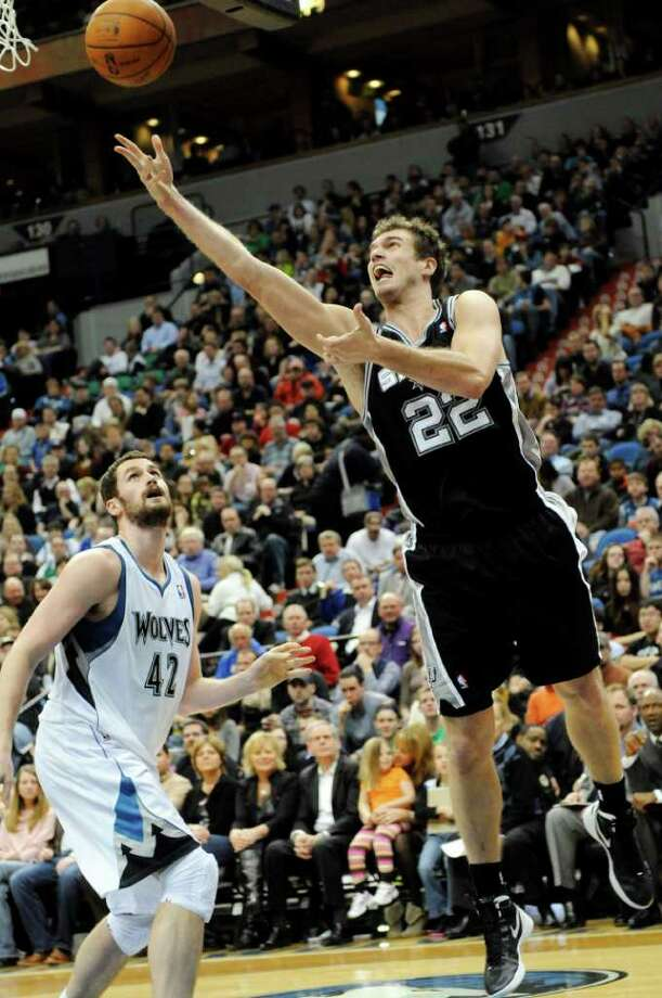 Minnesota Timberwolves' Kevin Love (42) watches as San Antonio Spurs' Tiago Splitter, of Brazil, shoots a layup in the second half of an NBA basketball game, Friday, Jan. 27, 2012, in Minneapolis. The Timberwolves won 87-79. (AP Photo/Jim Mone) Photo: Associated Press