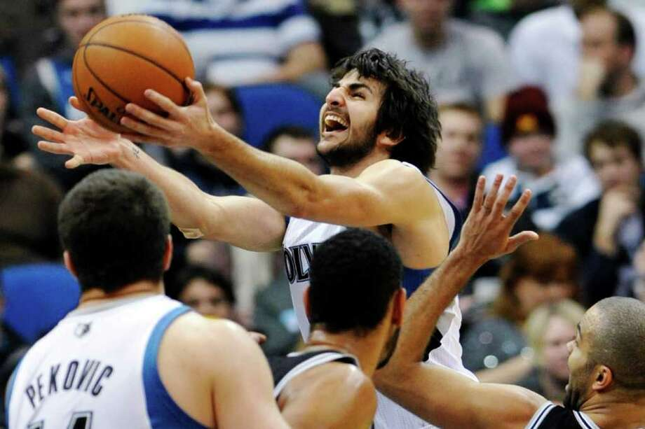 Minnesota Timberwolves' Ricky Rubio, of Spain, shoots a layup past San Antonio Spurs' Tony Parker, of France, right, in the second half of an NBA basketball game, Friday, Jan. 27, 2012, in Minneapolis. Rubio contributed 18 points and 10 assists as the Timberwolves won 87-79. (AP Photo/Jim Mone) Photo: Associated Press