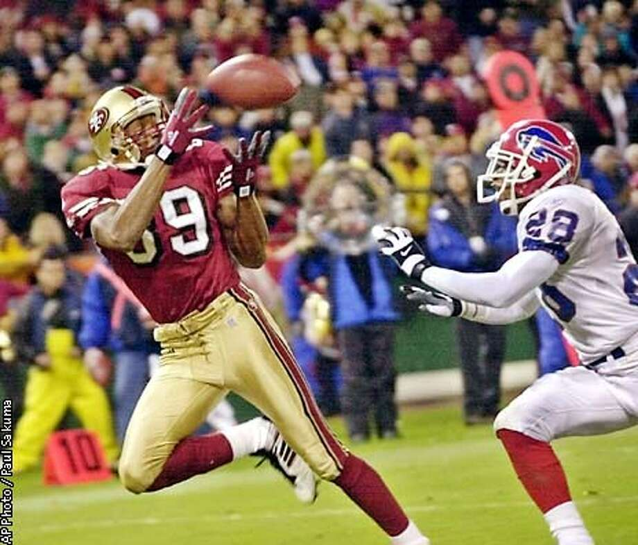 San Francisco 49ers wide receiver Tai Streets catches a 23-yard touchdown pass from quarterback Jeff Garcia in front of Buffalo Bills safety Travares Tillman in the second quarter in San Francisco, Sunday, Dec. 2, 2001. (AP Photo/Paul Sakuma) Photo: PAUL SAKUMA