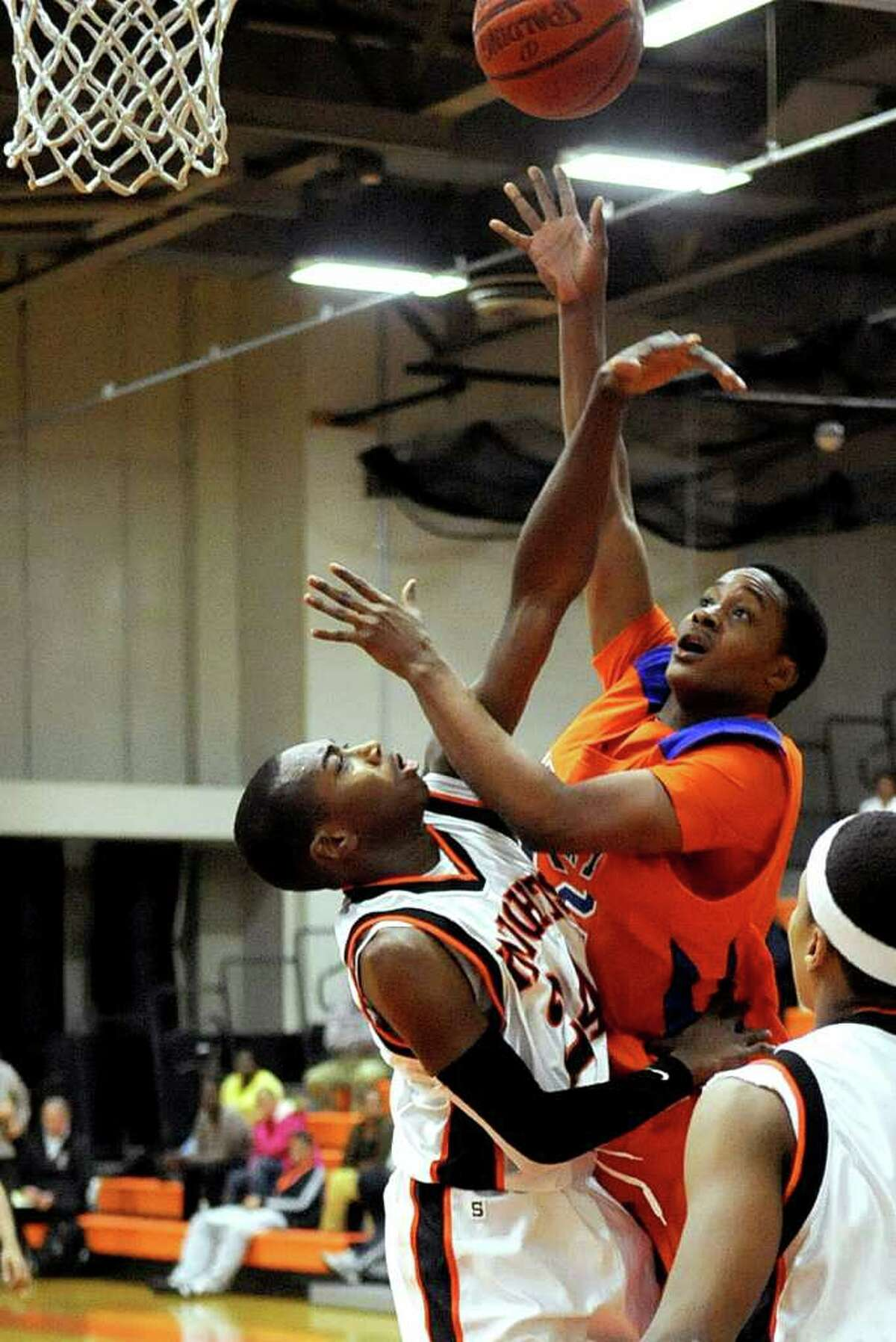 Danbury's C.J. Neptune looks for a basket as he is defended by Stamford's Kenny Wright during Friday's game in Stamford on January 27, 2012.
