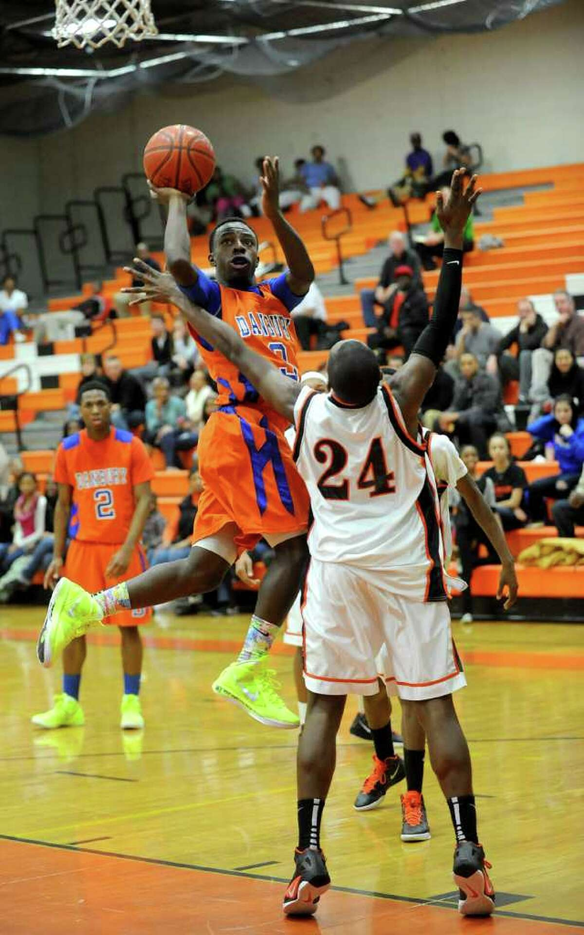 Danbury's James Harrington takes a shot as he is guarded by Stamford's Kenny Wright during Friday's game in Stamford on January 27, 2012.
