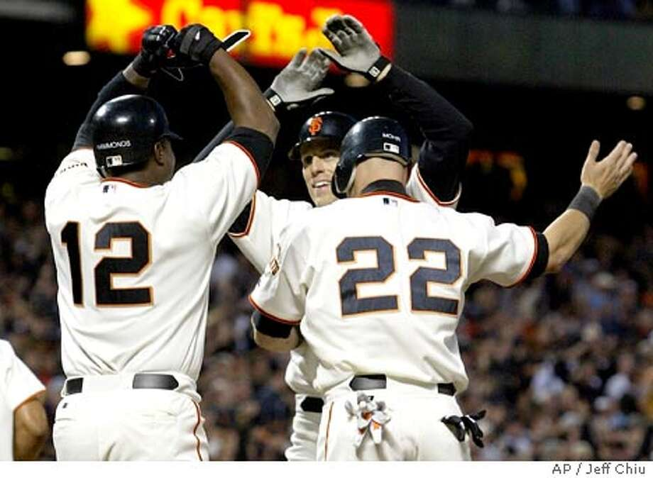 San Francisco Giants' Brian Dallimore, center, is congratulated by teammates Jeffrey Hammonds, left, and Dustan Mohr after hitting a grand slam in the second inning against the Florida Marlins in San Francisco on Friday, April 30, 2004. (AP Photo/Jeff Chiu) Photo: JEFF CHIU