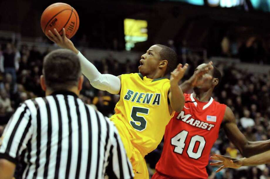 Siena's Evan Hymes (5), center, shoots and makes the shot and draws a foul from Marist's Chavaughn Lewis (40) during their basketball game on Friday, Jan. 27, 2012, at Times Union Center in Albany, N.Y. Siena wins 66-55. (Cindy Schultz / Times Union) Photo: Cindy Schultz / 00015373J