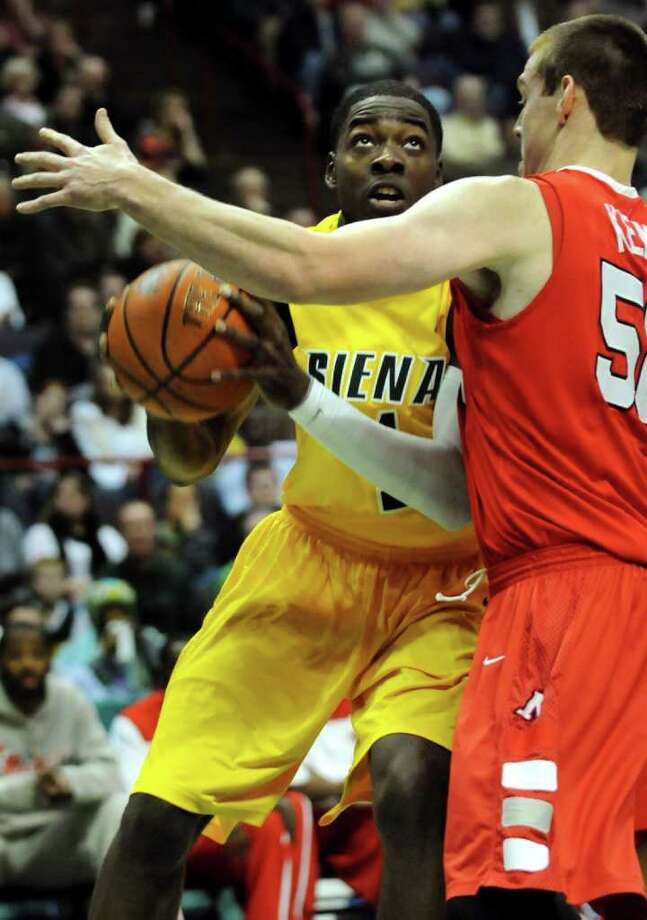 Siena's OD Anoskie (1), center, looks to the hoop as Marist's Adam Kemp (50) defends during their basketball game on Friday, Jan. 27, 2012, at Times Union Center in Albany, N.Y. (Cindy Schultz / Times Union) Photo: Cindy Schultz / 00015373J