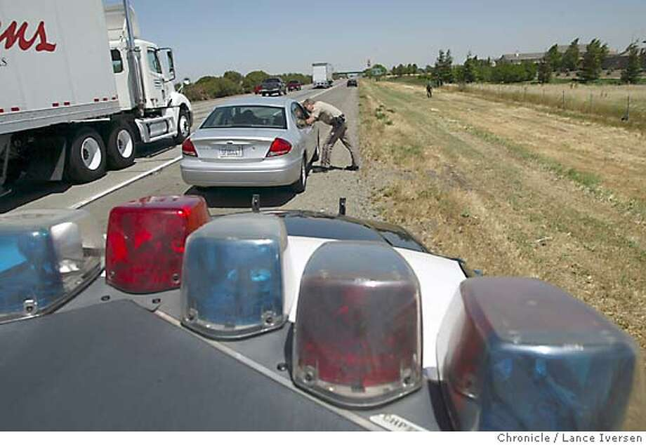 "SPEEDERS29_097_LI.JPG event on 4/28/04 in FAIRFIELD Officer Mark Pieschke writes a ticket to a Richmond motorist clocked at over 80mph from the air. CHP crackdown on I-80 speeders. New radar guns and ""LIDAR"" guns. Airplanes and hundreds of officers between the Bay Bridge in San Francisco to the Nevada border ticketed hundreds of drivers for going as little as 5 mph over limit. However most were going 15 to 35 mph over the posted 65 limit.  By Lance Iversen/The San Francisco Chronicle Photo: Lance Iversen"
