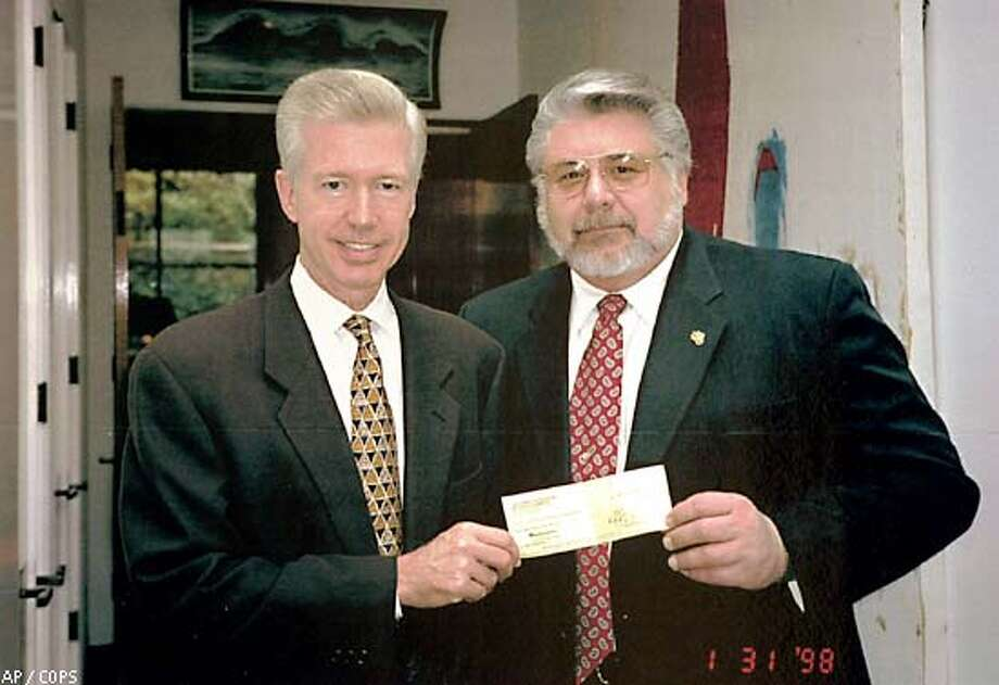Monty Holden, the executive director of the California Organization of Police and Sheriffs provided this photograph Tuesday Oct. 8, 2002, that allegedly shows then Lt. Gov. Gray Davis, left, illegally accepting a check from COPS' former Executive Director Al Angele at his state Capitol office. (AP Photo/California Organization of Police and Sheriffs/HO)