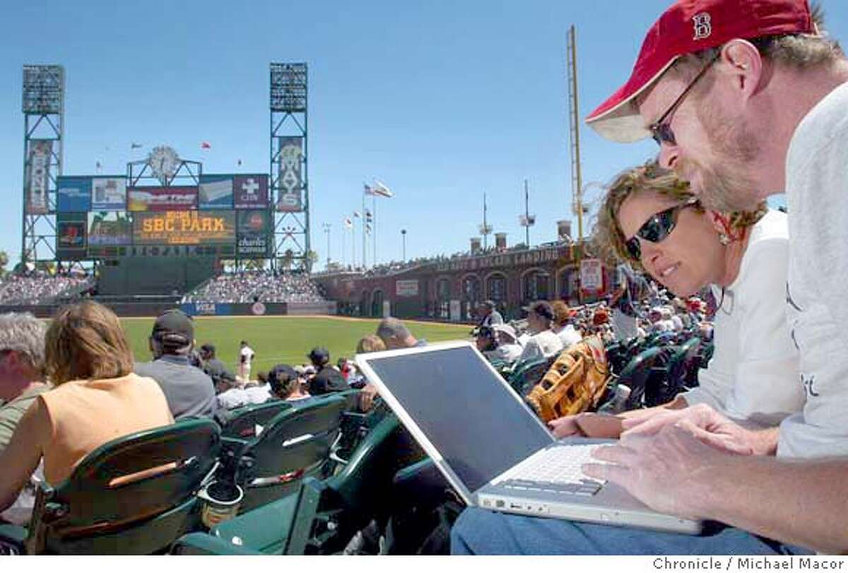 Michelle Bercow, Menlo Park, and Al Grayson, SF, share a laptop while connected to the internet through a free service at the ballpark, sitting in section 105 row 15 down the first base lineWiFi Internet access now available to fans who take in a Giants game at SBC Park here in San Francisco. event on 4/22/04 in San Francisco Michael Macor / San Francisco Chronicle