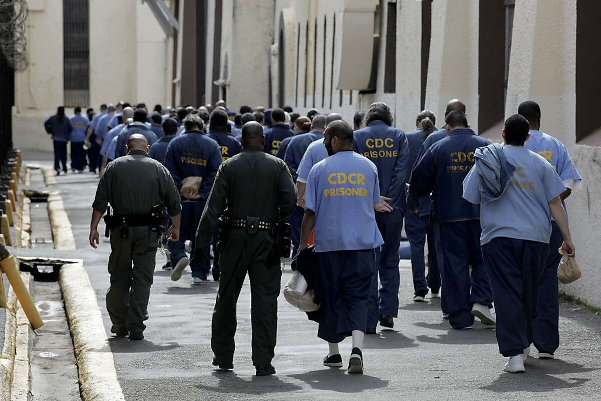 Corrections officers, lead prisoners back to their housing inside San Quentin State Prison.