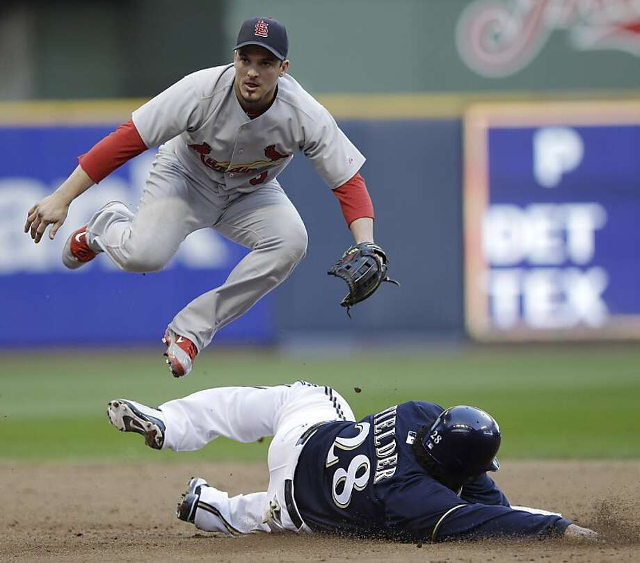 St. Louis Cardinals second baseman Ryan Theriot leaps over Milwaukee Brewers' Prince Fielder (28) to turn a double play on a ball hit by Rickie Weeks during the sixth inning of Game 1 of baseball's National League championship series Sunday, Oct. 9, 2011, in Milwaukee. (AP Photo/David J. Phillip) Photo: David J. Phillip, Associated Press