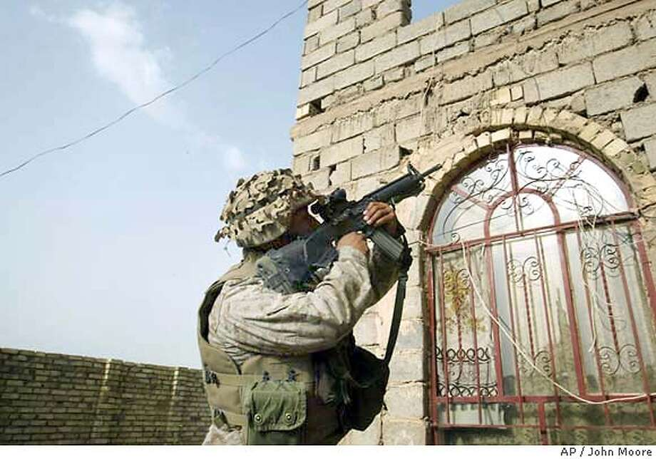 A U.S. Marine from the 1st Battalion 5th Marines prepares to enter a house to search for Iraqi insurgents on the outskirts of Fallujah, Iraq Friday, April 23, 2004. (AP Photo/John Moore) Photo: JOHN MOORE