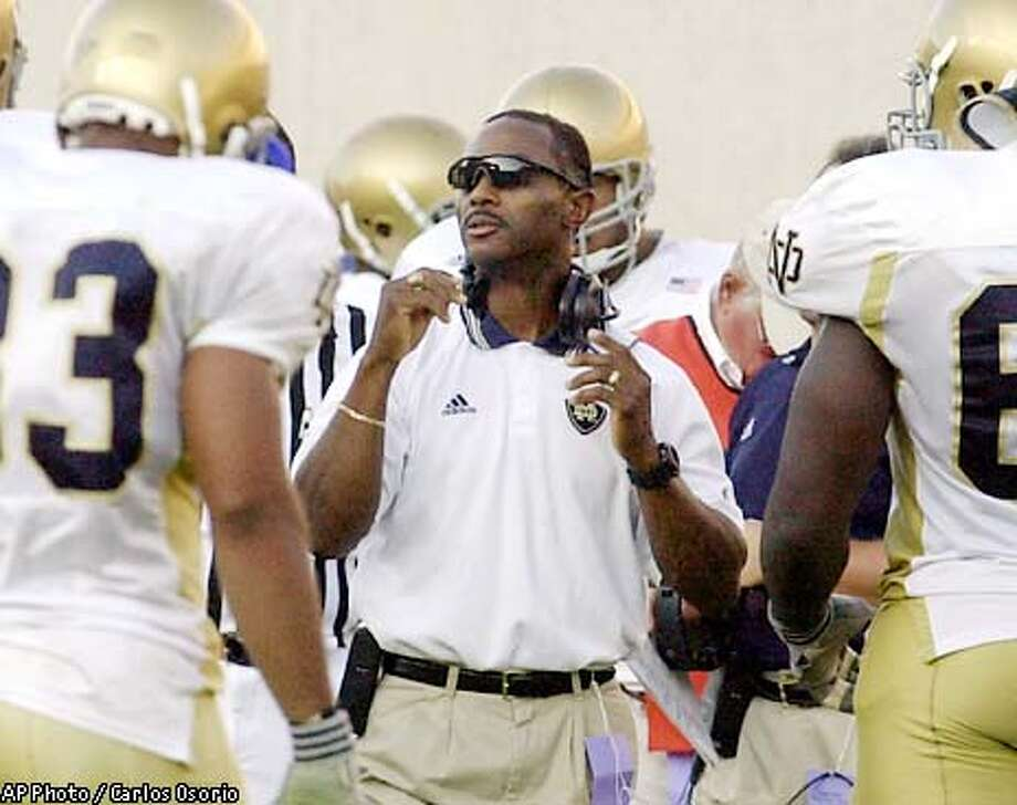 Notre Dame head football coach Tyrone Willingham prepares to talk to his team during the fourth quarter of their game against Michigan State in East Lansing, Saturday, Sept. 21, 2002. Just four games into the gamble of his professional life, Willingham's future looks so bright, he has to wear shades. Some 24 hours earlier, a last-minute win at Michigan State kept Notre Dame's newest coach undefeated. His team is already looking forward to next weekend off. (AP Photo/Carlos Osorio) Photo: CARLOS OSORIO