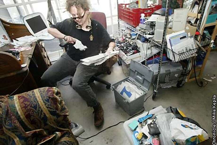 "Lile Elam with Geekmaid wades through a clinents home office clutter. Elam's goal is to set up organizational systems that work for computer ""Geeks"" and their often busy schedule. BY MIKE KEPKA/THE CHRONICLE Photo: MIKE KEPKA"