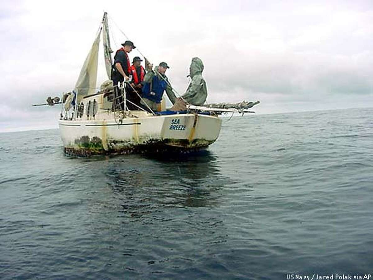 Sailors from the U.S. Navy frigate McClusky speak to Richard Van Pham, right, aboard Pham's sailboat Sept. 17, 2002, after they found him adrift off the coast of Costa Rica. Van Pham was rescued after being adrift aboard his damaged sailboat at sea for more than three months, keeping himself alive by catching fish, seabirds and turtles for food. (AP Photo/U.S. Navy via The San Diego Union-Tribune, Jared Polak)