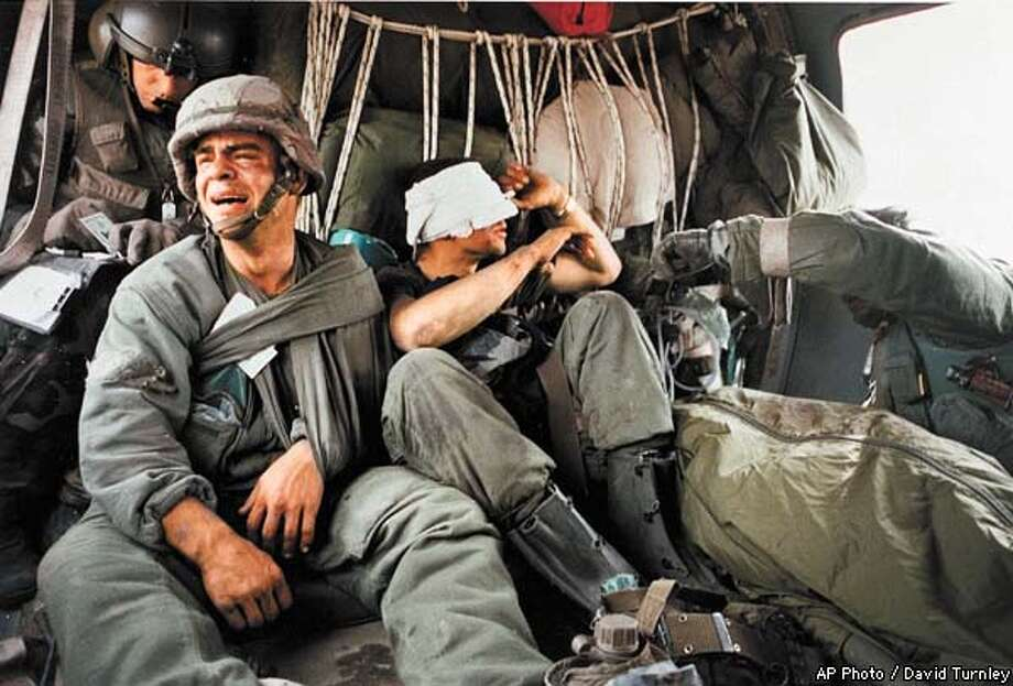 Ken Kozakiewicz, 23, left, cries after being given the dogtags and thus learning of the death of a fellow tank crewman, bodybag at right, on Feb 28, 1991. The soldiers are from the 24th Mechanized Infantry Division. At right is wounded comrade Michael Santarakis, 21. The casualties incurred when a mortar of undetermined origin struck their tank in the battle of the Euphrates Valley during the Persian Gulf War. (AP Photo/DOD POOL/David Turnley) Photo: DAVID TURNLEY