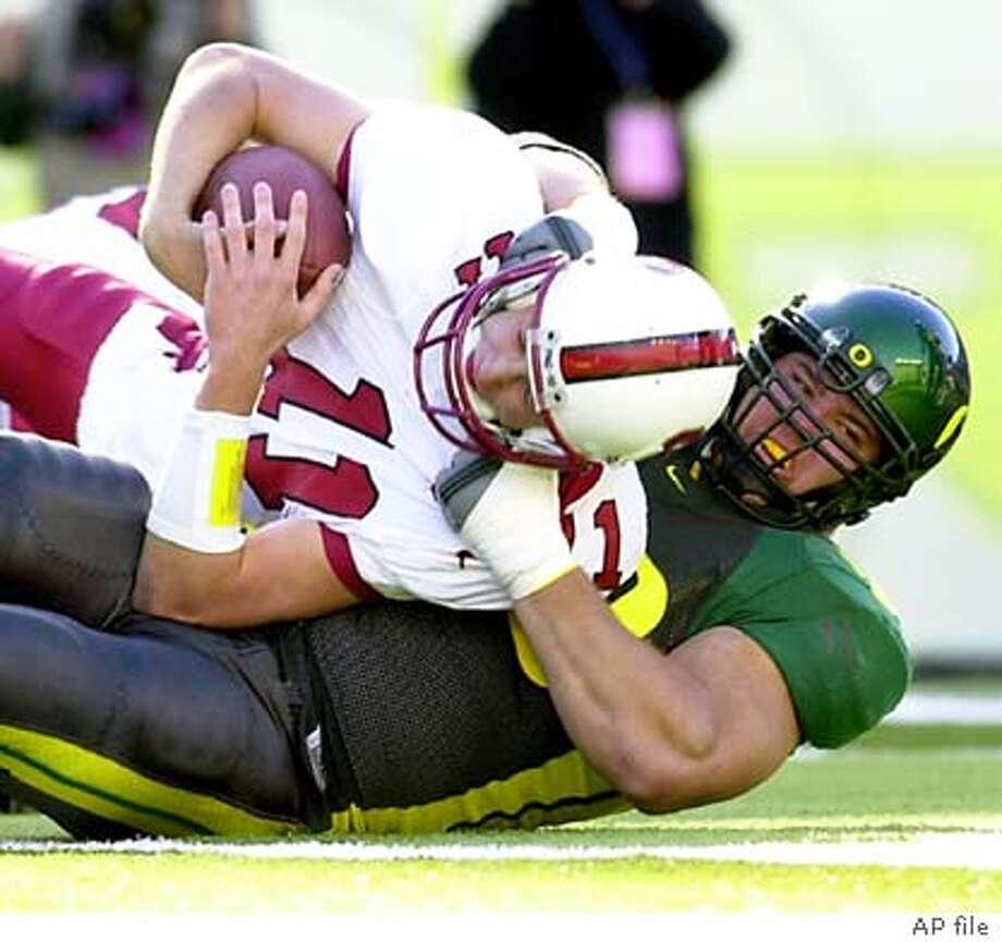 Oregon defender Igor Olshansky, right, sacks Stanford quarterback Kyle Matter during Pac-10 football action in Eugene, Ore., Saturday, Nov. 2, 2002, as Oregon beats Stanford, 41-14. (AP Photo/Don Ryan) Photo: DON RYAN