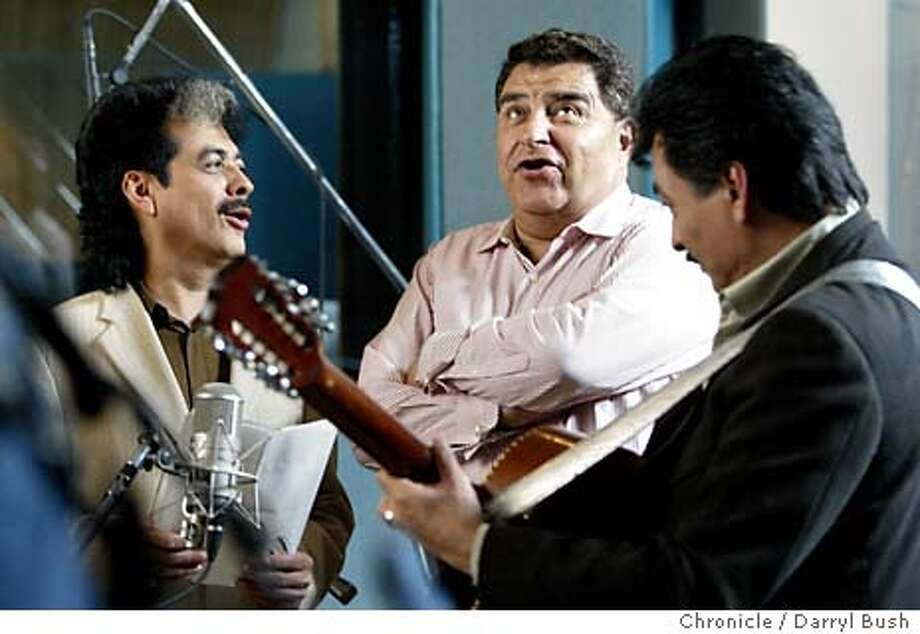 Don Francisco, a Mexico television personality, center, sings in a duet with singer Hernan Hernandez, left, and Eduardo Hernandez, right foreground, of the band, Los Tigres, who are playing their Tehano music for an in studio video taping. Event on 4/1/04 in Menlo Park.  Darryl Bush / The Chronicle Photo: Darryl Bush