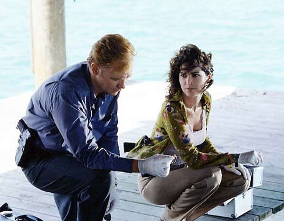 "caption: ""Wet Foot, Dry Foot"" -- When a tatoo on the remains of a human torso discovered in a tiger shark's stomach identifies the victim as a political prisoner from Cuba, the CSI team follows a trail that uncovers a secret mission for freedom that went terribly awry. Horation Caine (David Caruso) and Megan Donner (Kim Delaney) work the case on CSI: MIAMI, scheduled to air this fall on the CBS Television Network.  copyright: Photo: Robert Voets/CBS  �2002 CBS Worldwide Inc. All Rights Reserved �2002 CBS WORLDWIDE INC. ALL RIGHTS RESERVED Photo: Robert Voets/CBS �2002 CBS WORLDWIDE INC. ALL RIGHTS RESERVED. Photo: ROBERT VOETS"