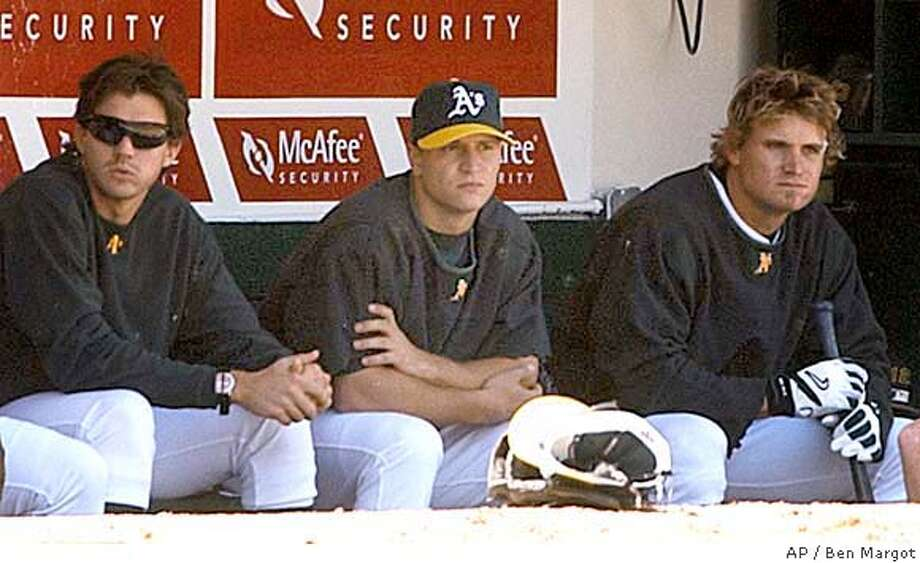 Oakland Athletics' Mark Ellis, center, sits in the dugout beside teammates Barry Zito, left, and Eric Byrnes during game against the Seattle Mariners, Saturday, April 10, 2004, in Oakland, Calif. Oakland Athletics second baseman Mark Ellis will miss the entire season with a right shoulder injury that requires surgery. Ellis, who has been rehabilitating in Phoenix, was in the Bay Area on Saturday to meet with team doctor Jerrald Goldman about the latest MRI on the shoulder. The test revealed a tornlabrum, and Goldman will perform the operation. (AP Photo/Ben Margot) Photo: BEN MARGOT
