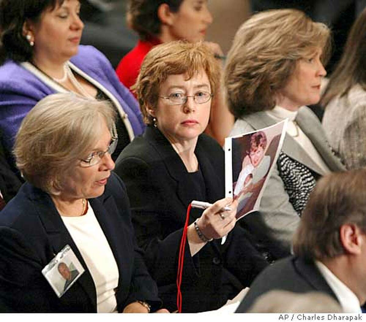 Terry McGowan, from New York City, center, holds a picture of her mother, who died in the South Tower of the World Trade Center during testimoney by National Security Adviser Condoleezza Rice to the independent commission investigating the Sept. 11 attacks Thursday, April 8, 2004, in Washington. (AP Photo/Charles Dharapak)