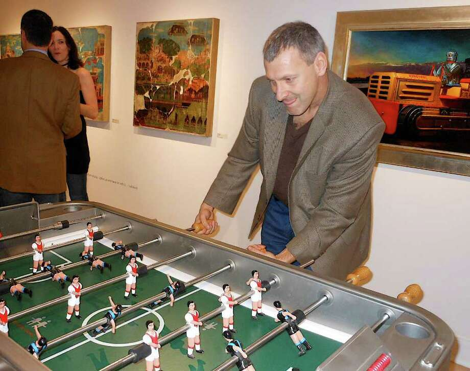 "Rob MacColl, of Westport, tackles a game of foosball, an interactive feature of the ""Toy Stories"" exhibit that opened Friday at the Westport Arts Center. Photo: Mike Lauterborn / Westport News contributed"