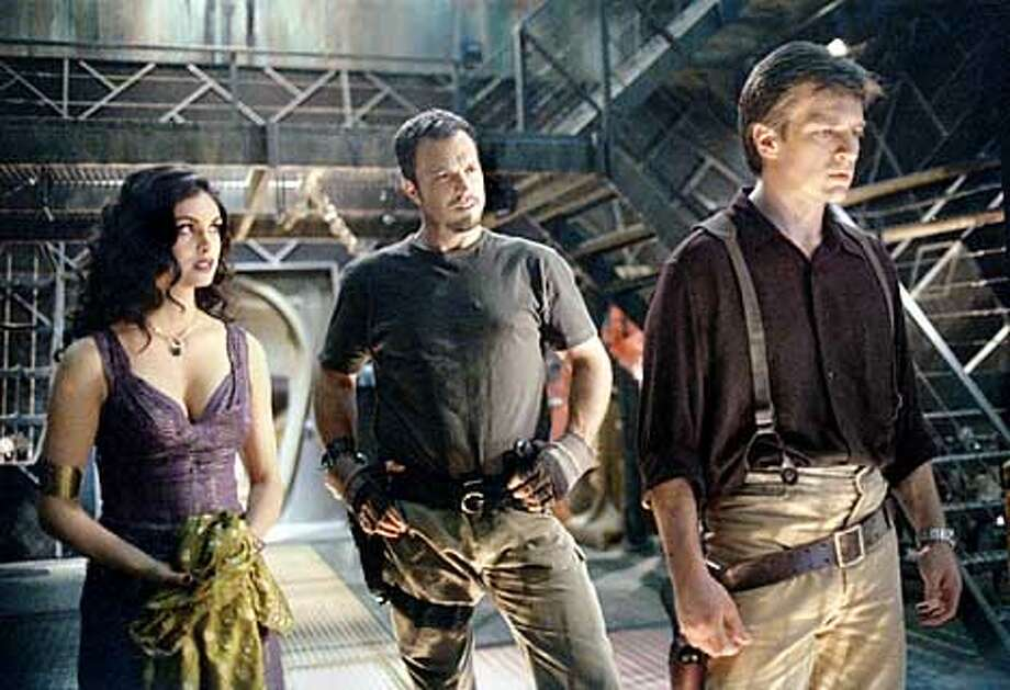 "L-R:Morena Baccarin as Inara, Adam baldwin as Jayne and Nathan Fillion as Capt. Malcolm ""Mal"" Reynolds in FIREFLY. ��2002FOX BROADCASTING CR:FOX  (HANDOUT PHOTO) Photo: HANDOUT"