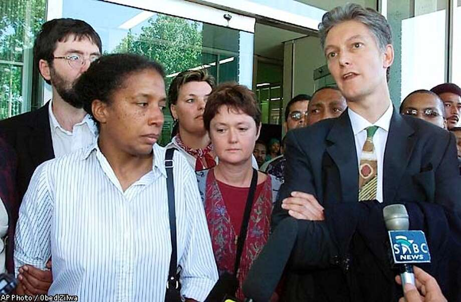 Attorney Mike Evans, right, lawyer for James Kilgore, and Kilgore's wife, Theresa Anne Barnes, left, speak outside the Cape Town, South Africa courthouse Monday Nov. 11, 2002. Kilgore, a former member of the Symbionese Liberation Army and one of the FBI's most wanted criminals was arrested Friday night in Cape Town after being on the run for 27 years. (AP Photo/Obed Zilwa) Photo: OBED ZILWA
