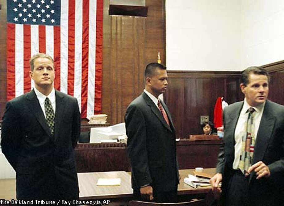 "Matthew Hornung, left, and Clarence ""Chuck"" Mabanag, center, two of four former Oakland police officers known as ""The Riders,"" and defense attorney Michael Rains are shown during a recess in the first day of the former officers' trial Thursday, Sept. 12, 2002, at Alameda County Superior Court in Oakland, Calif. A third officer, Jude Siapno, is also on trial while the fourth, Frank Vazquez, remains fugitive. A prosecutor in the case said the officers systematically set up young black men and conjured false accusations against them to feed their egos. (AP Photo/The Oakland Tribune, Ray Chavez) Photo: RAY CHAVEZ"