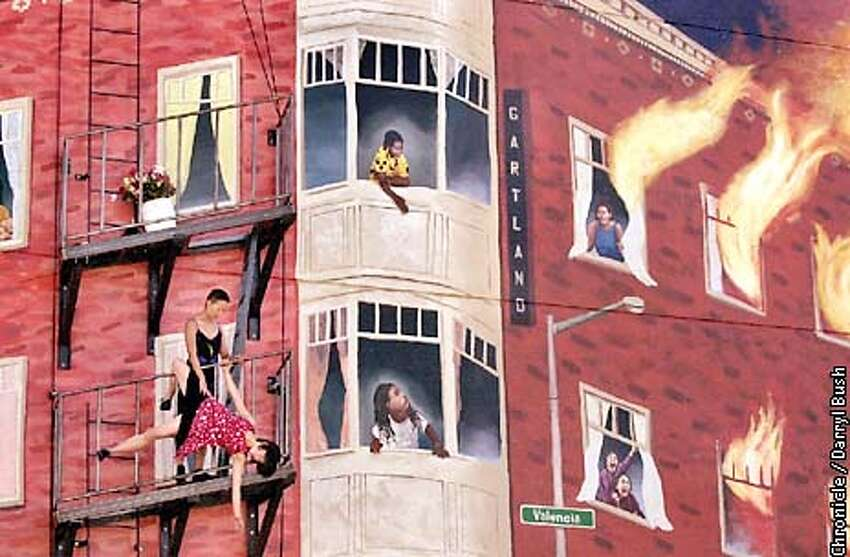 Tamara Welch (standing) and Yayoi Kambara (hanging upside down) of Mission Wall Dances dance on a fire escape balcony, bottom left, as they perform