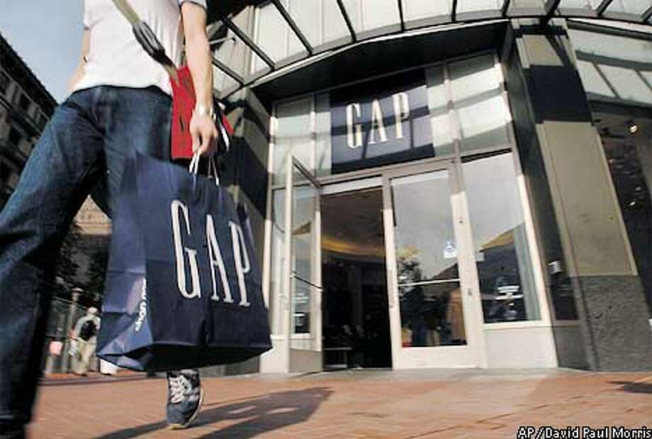 A shopper leaves a Gap store in San Francisco, Tuesday, Nov. 12, 2002. The San Francisco-based company's 3,158 stores have been restocked with more basic clothing designed to appeal to mainstream tastes and its catchy ads appear to be luring back once-alienated customers. (AP Photo/David Paul Morris) Photo: DAVID PAUL MORRIS