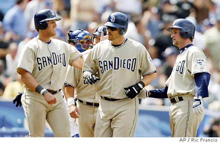 San Diego Padres' Phil Nevin, center, is congratulated by teammates Sean Burroughs, left, and Brian Lawrence, right, after hitting a grandslam in the fifth inning against the Dodgers to give the Padres a 5-0 lead Monday, March 5, 2004, at Dodgers Stadium in Los Angeles. (AP Photo/Ric Francis) Photo: RIC FRANCIS