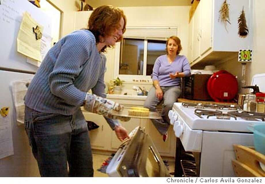Kory O'Rourke, seated, watches as her wife, Kate Sheppard, prepares dinner on Tuesday night, March 30, 2004, in their San Francisco, Ca., home. The couple have been married since February 13, 2004, when Same-Sex Marriage licenses were issued to gay and lesbian couples in the city, and now they are testing the waters of whether employers will honor their licenses. Photo taken on 03/30/04, in San Francisco, Ca. Photo by Carlos Avila Gonzalez/The San Francisco Chronicle Photo: Carlos Avila Gonzalez
